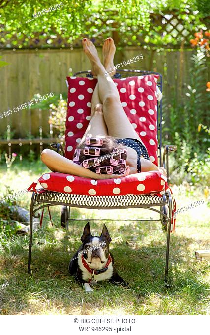Woman with rollers in her hair lounges in her garden with a Boston Terrier