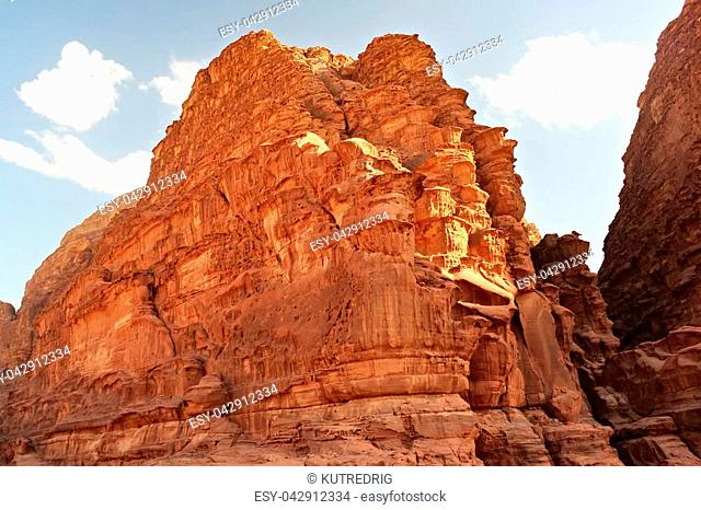 Red stone walls of the canyon of Wadi Rum desert in Jordan. Wadi Rum also known as The Valley of the Moon is a valley cut into the sandstone and granite rock in...