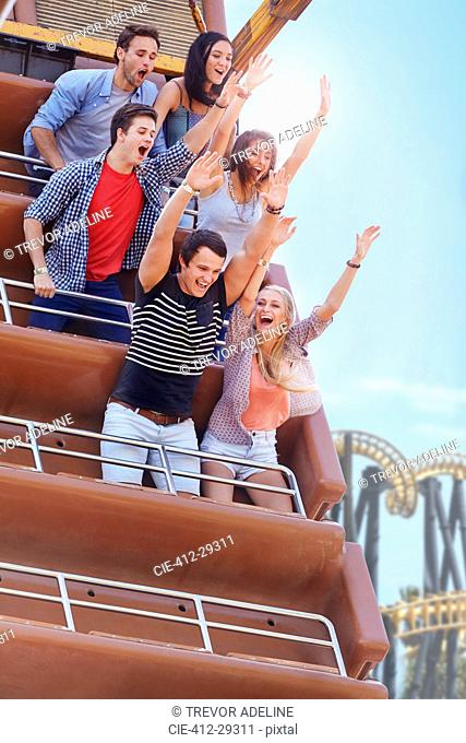 Enthusiastic friends cheering on amusement park ride