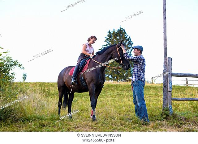 Couple with horse in rural pasture