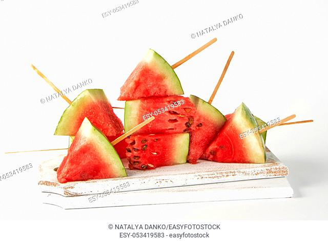 sliced ripe red watermelon with seeds on a wooden white cutting board, summer berry