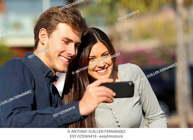 Happy couple watching media in a smart phone outdoors with an urban background