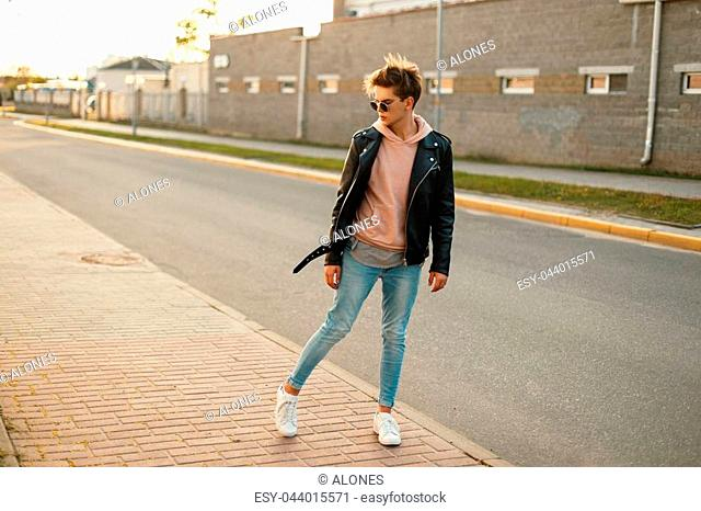 Handsome young man with sunglasses in a black leather jacket, blue jeans and white shoes on the street near the road