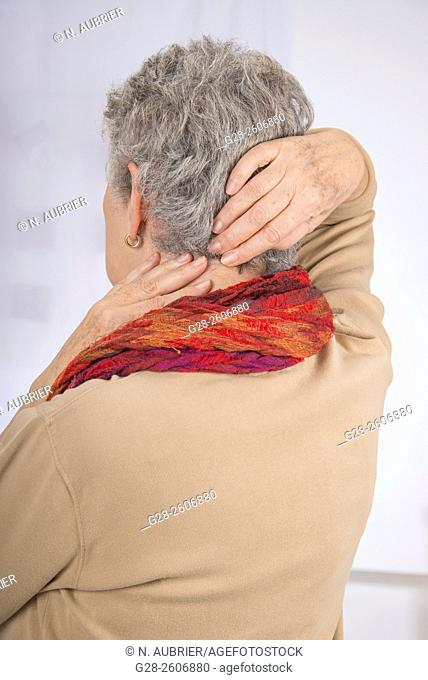 Senior woman with grey hair, seen from behind, suffering from a neck pain, trying to relieve pain by massaging her back