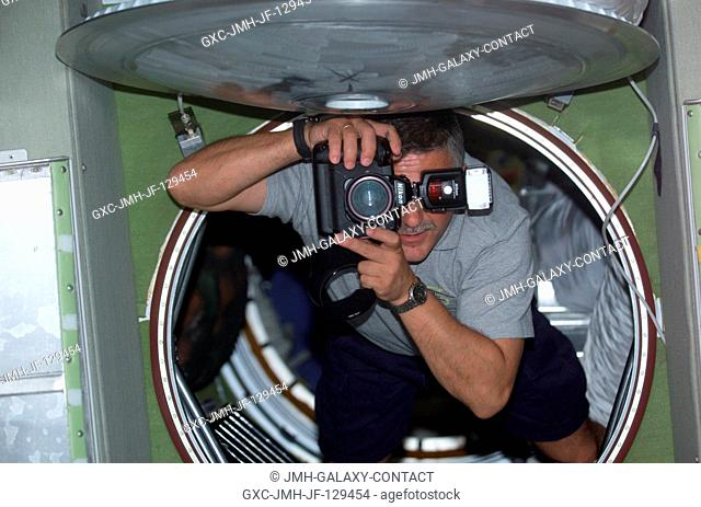 Cosmonaut Fyodor N. Yurchikhin, STS-112 mission specialist, uses a still photo camera while floating into the Zvezda Service Module on the International Space...