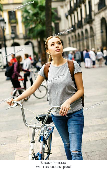 Spain, Barcelona, young woman pushing bicycle in the city