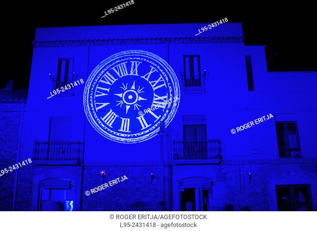 Light projection of a watchless clock over medieval city as part of the feast setup