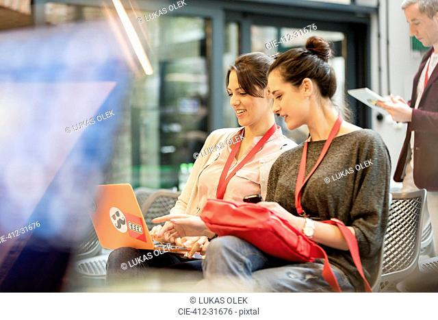 Female college students using laptop