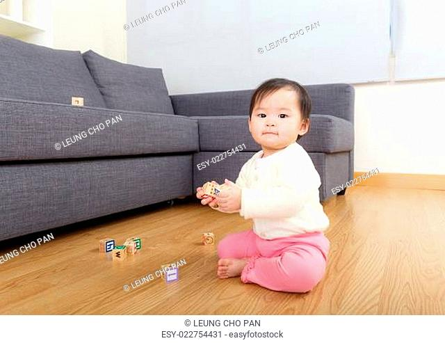 Asia baby girl play toy block at home