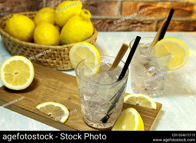 two glasses of lemonade with ice, spoon and straw on cutting board, cut lemons and basket with lemons on red brick bacground