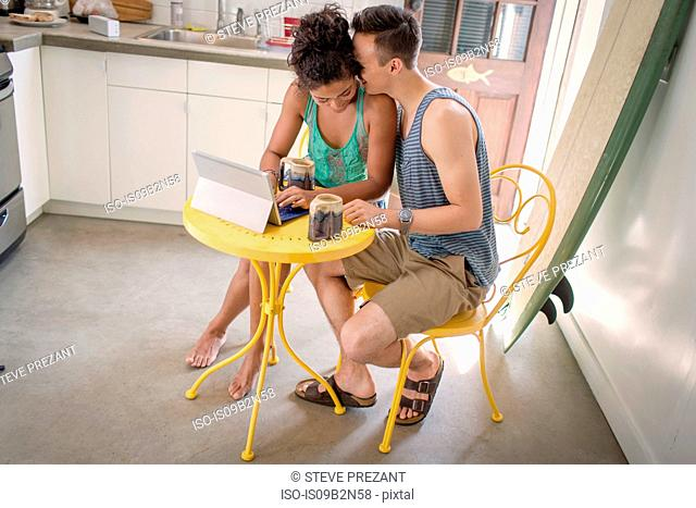 Couple at table using digital tablet