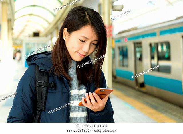 Woman reading message on cellphone in train station