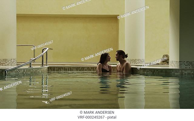 WS Couple kissing in indoor swimming pool / Petriolo,Marche,Italy