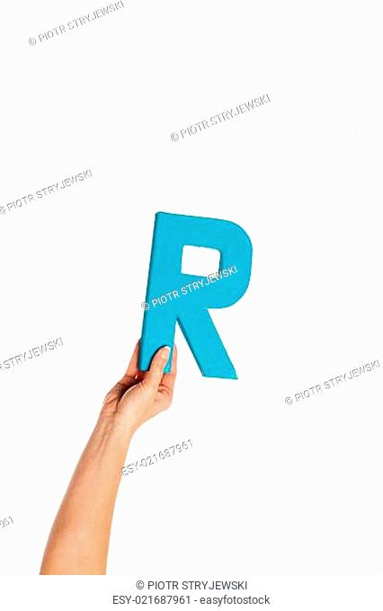 hand holding up the letter R from the bottom