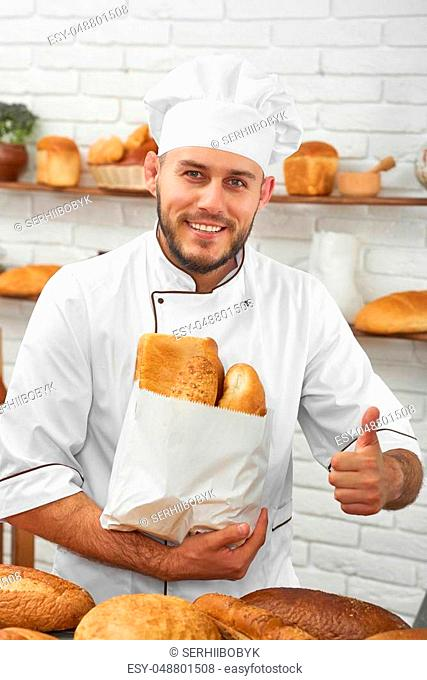 Vertical portrait of a handsome young baker smiling joyfully to the camera showing thumbs up holding a paper bag with freshly baked delicious bread