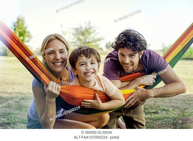 Family relaxing together outdoors, portrait