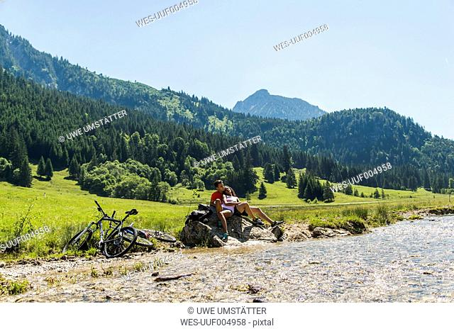 Austria, Tyrol, Tannheim Valley, young couple with mountain bikes relaxing at brook