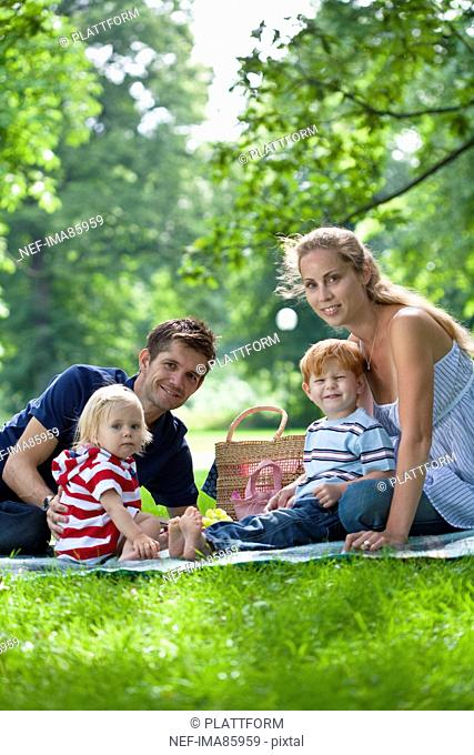 parents with children sitting in park and looking at camera
