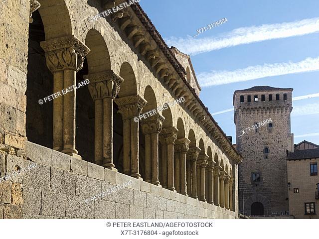 The Romanesque, arcaded portico of San Martin church, looking towards the Torreón de Lozoya in the Plaza Medina del Campo, Segovia, Spain