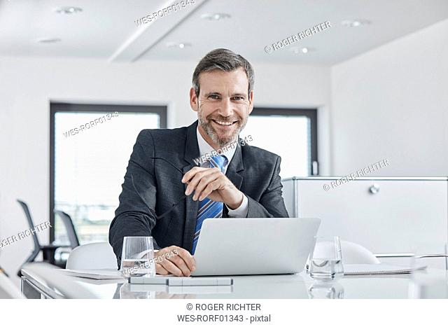 Portrait of smiling businessman with laptop at desk in office
