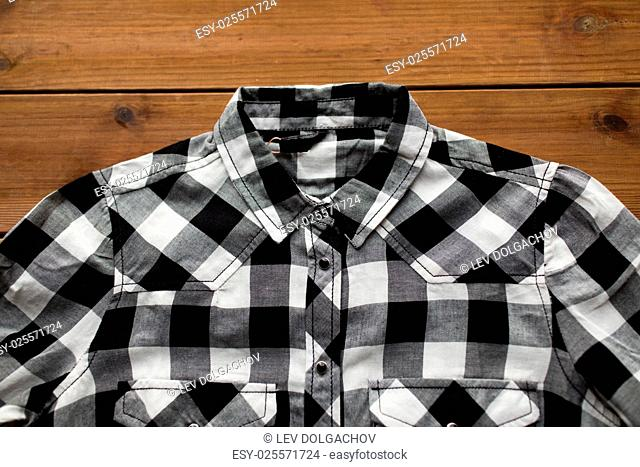 laundry, clothes, fashion and objects concept - close up of checkered shirt on wooden background
