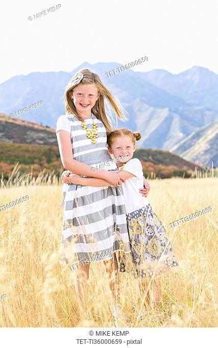 USA, Utah, Provo, Two girls (4-5, 8-9) standing in field