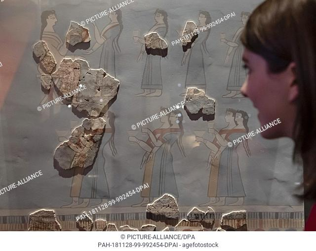 26 November 2018, Baden-Wuerttemberg, Karlsruhe: A person in the Badisches Landesmuseum in Karlsruhe Castle looks at fragments of a processional fresco