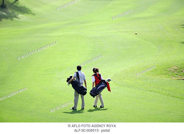Couple Walks Down the Fairway of a Golf Course