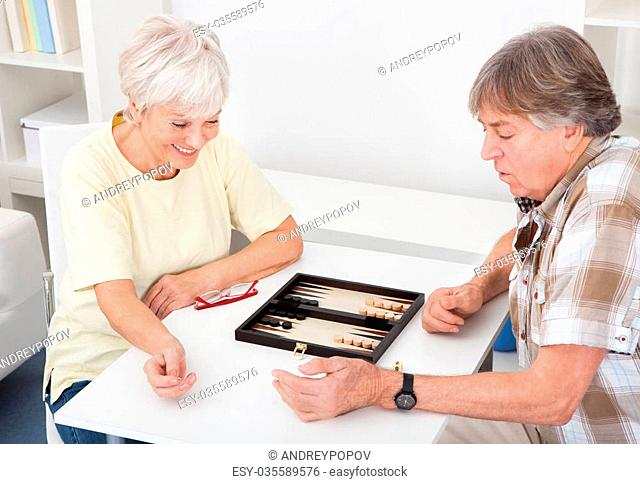 Happy Senior Couple Playing Game Of Backgammon At Home