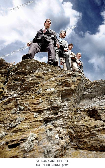 Businessmen peering over cliff edge