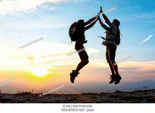 Italy, Monte Nerone, two happy and successful hikers jumping in the mountains at sunset