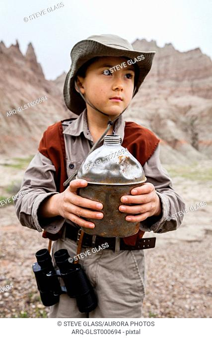 A 6 year old Japanese American boy dressed as an explorer with a hat and vest surveys the land (eroding rock formations) while binoculars hang on his side and...