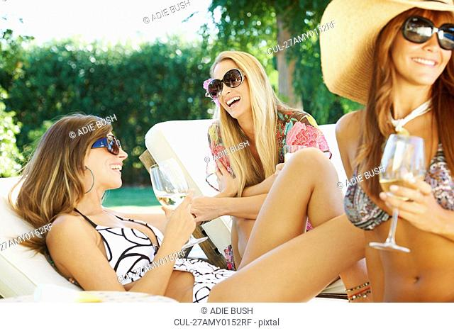 Girls relaxing by the pool on sun beds
