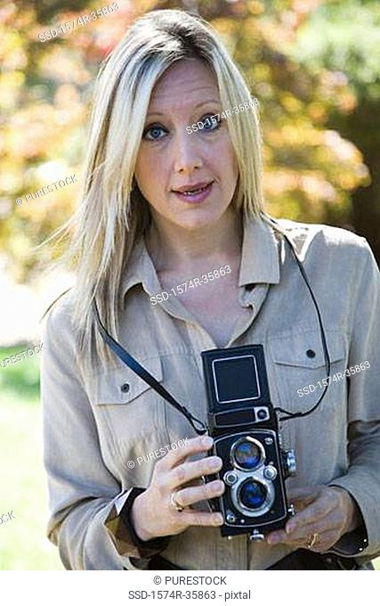 Portrait of woman holding twin lens camera