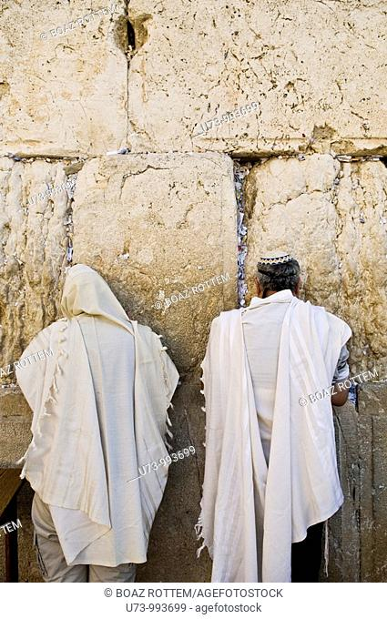 Two Jewish men pray at the holy wailing wall in the old city of Jerusalem.Jews believe that the wailing wall is the western wall of the Jewish temple which was...