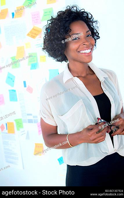 Portrait of female office worker holding spectacles