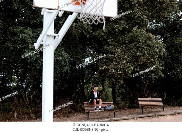Male teenage basketball player sitting on park bench by basketball court