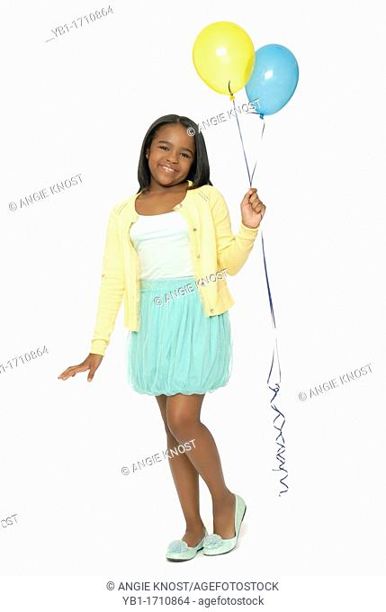 Cute ten year old African American girl holding balloons and smiling  She is wearing a fashionable blue-green skirt and yellow jumper