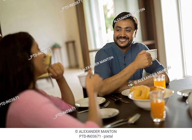 Man and woman at breakfast table with coffee cups smiling at each other