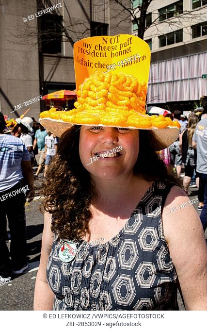 New York, NY - April 16, 2017. A woman at New York's annual Easter Bonnet Parade and Festival on Fifth Avenue wears a hat covered in cheese puffs