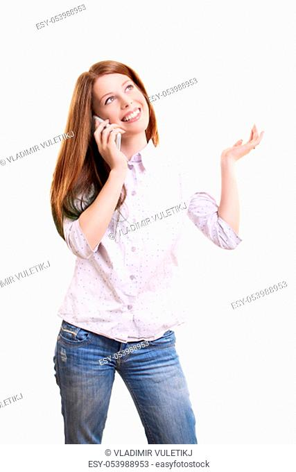 Smiling beautiful young woman in casual clothing talking on a phone and gesturing with one hand, isolated on white background