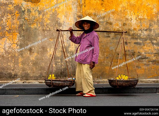 Old Woman from Vietnam is selling fruits in the Streets of Hoi An