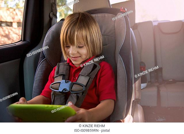 Girl in car safety seat looking at digital tablet