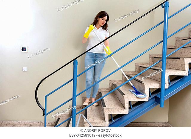 Young Female Janitor Cleaning Staircase With Mop