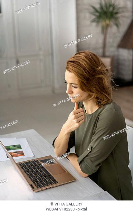 Young woman working in office, using laptop