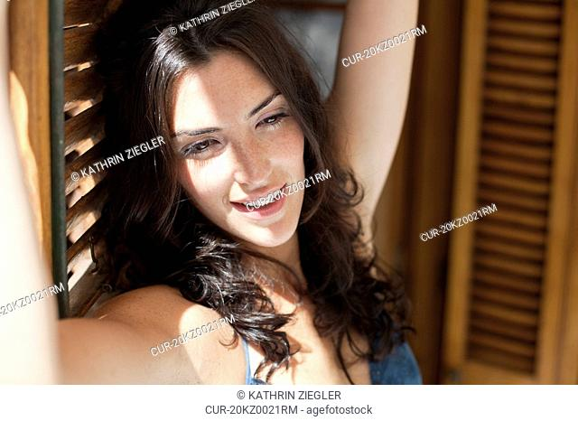 Woman leaning against open blinds