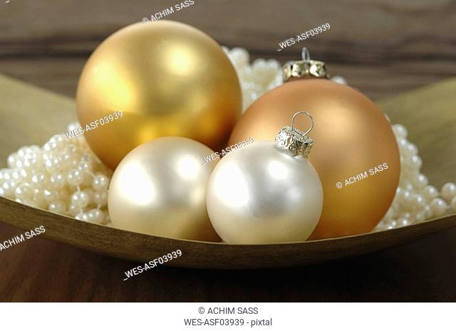 Christmas decoration, Christmas baubles and pearls in bowl, close-up