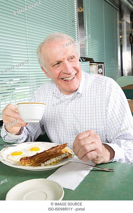 Senior man eating a fried breakfast