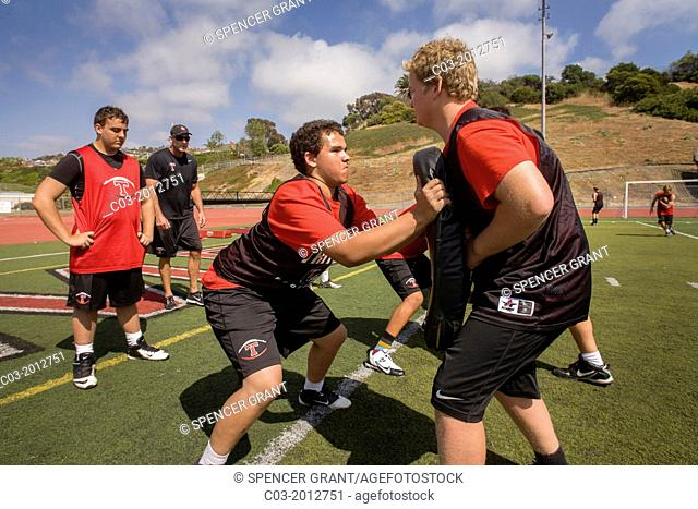 Using protective pads, multiethnic high school athletes practice tackling at spring football practice in San Clemente, CA