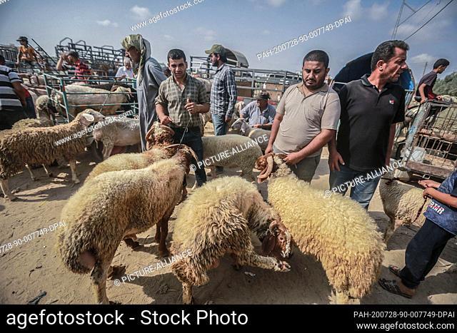 28 July 2020, Palestinian Territories, Deir al Balah: Cattle traders and customers gather at Deir al Balah livestock market ahead of the Muslim's holiday of Eid...